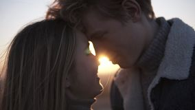Close up footage of romantic young couple face to face backlit by the sun with flare effect while standing on the roof stock footage