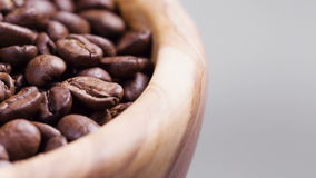 Close up footage of rotating roasted coffee beans in wood bowl stock footage