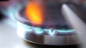 Gas stove. Close up footage of a stainless steel stove gas flame burner being turned on and off while also being controlled stock video footage