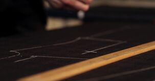 Close up footage of a tailor drawing lines on fabric and making some alterations around the cut with his chalk