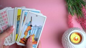 Close up footage of two hands shuffling and adjusting tarot cards