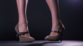 Close-up footage woman with crooked legs standing on high hills on black background, moving her feet stock footage