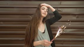 Close up footage of woman holding sparkler in her hands on the street in front of brown wall, slow-motion. Shot, retro color stock video