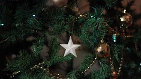 Close up footage of a woman`s hand hanging balls on a christmas tree. stock footage