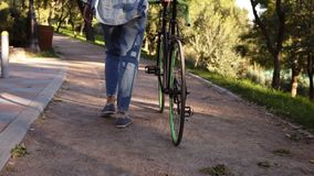 Close up footage of woman in sneakers walking besides a bicycle in the morning park or street. Rare view of a young