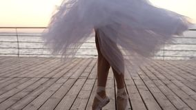 Close up footage of young ballerina`s legs in dance motion. Ballet dancer in long white tutu and pointe exercising stock footage
