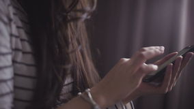 Close-up footage of young female hands who are using smartphone to write a message. Close-up footage of  young female hands who are using smartphone to write a stock video