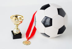 Close up of football ball, golden cup and medal Royalty Free Stock Photos