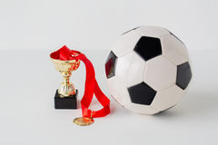 Close up of football ball, golden cup and medal Stock Photography