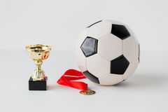 Close up of football ball, golden cup and medal Royalty Free Stock Photo