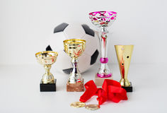 Close up of football ball, golden cups and medals Royalty Free Stock Image