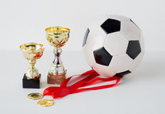 Close up of football ball, golden cups and medals Stock Image