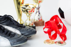 Close up of football boots, cups and medals Stock Photos