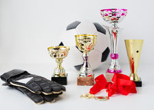 Close up of football, gloves, cups and medals Royalty Free Stock Photos