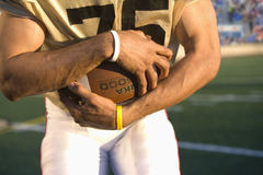 Close up of football player holding football Stock Photos
