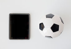 Close up of football or soccer ball and tablet pc Stock Photos