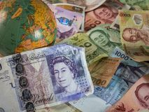 Close up of foreign banknotes with british currency and globe. Close up of foreign banknotes with british currency and map stock photos