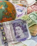Close up of foreign banknotes with british currency and globe. Close up of foreign banknotes with british currency and map royalty free stock images