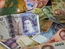 Close up of foreign banknotes with british currency and map. Close up of foreign banknotes with british currency and globe royalty free stock image