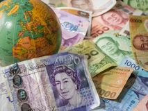 Close up of foreign banknotes with british money and map stock photos