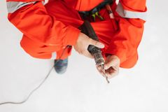 Close up foreman in orange work clothes holding drill machine in. Hands at work royalty free stock photography