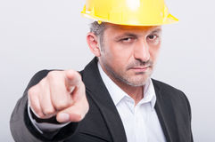 Close-up of foreman wearing hardhat pointing camera Stock Photography
