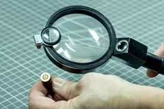 A forensic service officer holds in his hand a magnifying lens and a cartridge from the firearm and will conduct a ballistic exami royalty free stock image