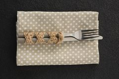 Fork and knife on a dotted napkin. Close-up of fork and knife on a dotted napkin Royalty Free Stock Photography