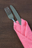 Close up fork and knife in tablecloth on wooden background. Stock Image