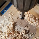 Forstner bit on bench drill. A close up of a Forstner bit on a stationary bench drill with wood shavings on table below Stock Images