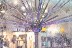 Close-up on a fountain with colored lights in the form of a dome spraying water. In different directions stock photos