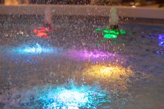 Close-up on a fountain with colored lights in the form of a dome spraying water. In different directions royalty free stock images
