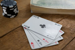 Close-up of four aces by chips and money Royalty Free Stock Images
