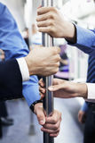 Close-up of four business people's hands holding the pole on the subway Royalty Free Stock Photography
