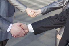 Close up of four business people shaking hands stock photos