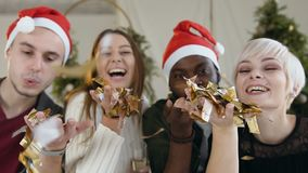 Close-up. Four cheerful of mixed race people are blowing a golden confetti from hands at the Christmas celebration or stock footage