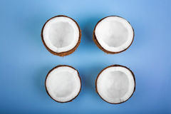 Close-up of four cut tropical coconuts on a light blue background. Delicious summer fruits. Nutritious exotic nuts. Stock Photos
