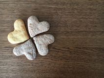 Close-up of four heart-formed cookies like shamrock leaves lying. On the wooden table background royalty free stock image