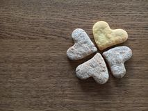 Close-up of four heart-formed cookies like shamrock leaves lying. On the wooden table background stock photos