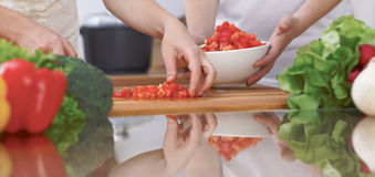 Close-up of four human hands are cooking in a kitchen. Friends having fun while preparing fresh salad. Vegetarian Stock Image