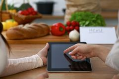 Close-up of four human hands are gesticulate over a tablet in the kitchen. Friends having fun while choosing menu or Stock Images