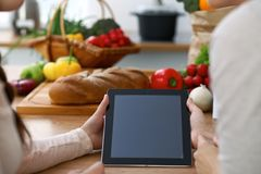 Close-up of four human hands are gesticulate over a tablet in the kitchen. Friends having fun while choosing menu or Royalty Free Stock Photos