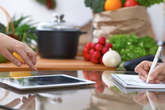 Close-up of four human hands are gesticulate over a tablet in the kitchen. Friends having fun while choosing menu or. Making online shopping. So much ideas for royalty free stock photos