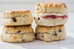 Traditional English cream teas, scones. Close up of four scones with jam and cream, on the plate, on the white wooden table, selective focus copy space for text Royalty Free Stock Photo