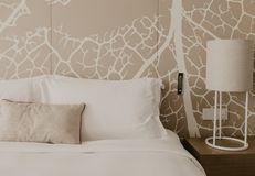 Close up fragment of bedroom with reading lamp in modern home or hotel royalty free stock photography