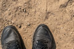 Close-up of a fragment of dusty sneakers on the sand and clay royalty free stock photos