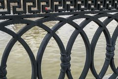 Close-up of fragment of an elegant cast iron fence of a bridge. royalty free stock photography