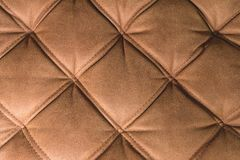 A close-up of a fragment of an expensive brown textile sofa in the room stock photography