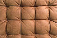 A close-up of a fragment of an expensive brown textile sofa in the room stock image