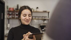 Close up frame of the barista who kindly accepts orders from the visitor